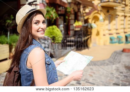 Happy female tourist is traveling by across the city. She is standing and holding a guide map. Woman is looking at camera and smiling