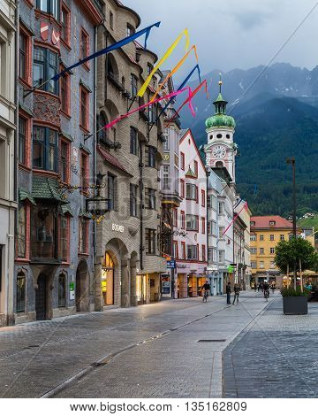 INNSBRUCK AUSTRIA - 18TH JUNE 2016: A view along Maria-Theresien-Strasse in Innsbruck during the day. The Hospital Church and the outside of buildings can be seen. Mountain can be seen in the distance.