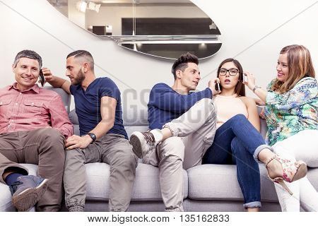 Group Of Friends On The Couch To The Phone At The Same Time