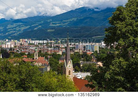 Part of the Innsbruck skyline during the day. Showing buildings churches mountains and clouds