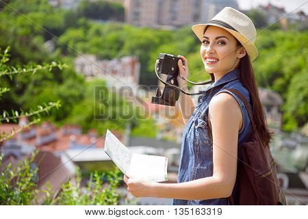 Happy young woman is making her journey. She is photographing town and smiling. Tourist is standing and holding map