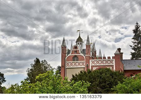 Woerlitzer Park gothic house in spring with cloudscape