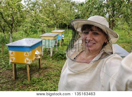 woman beekeeper making selfie near beehives apiary