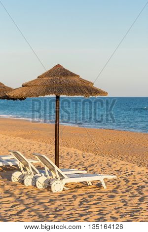 Sun beds and umbrellas to tourists. Portuguese beach in the Algarve.