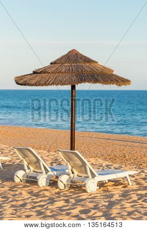 Sun beds and umbrellas to tourists in the summer. Portuguese beach in the Algarve.