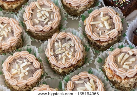 Cream cakes in paper baskets. Close-up on birthday.