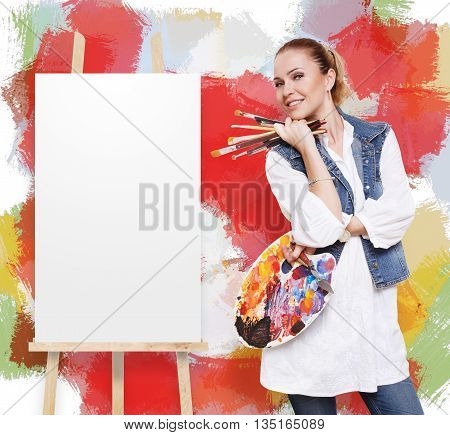 Woman artist with art tools. Female painter with brushes and palette stands by empty canvas at easel near colorful wall with copy space. Fine art school. Art classes for adults, education concept.