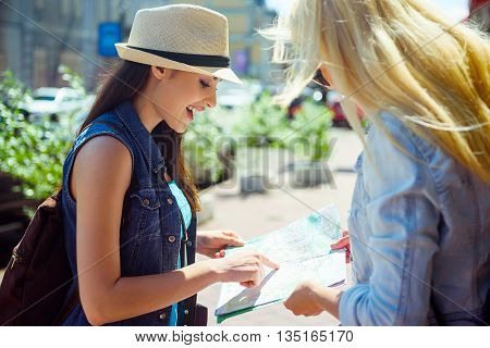 Cute female tourist is asking the way in passer-by. She is pointing finger at map and smiling. Girl is standing in city