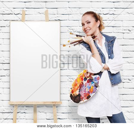 Happy artist. Woman artist with art tools. Girl painter with brushes and palette. Empty canvas at easel at white brick wall with copy space. Fine art. Art classes for adults, education concept.