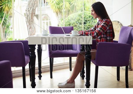 Sideview of young attractive dark-haired woman in casual clothes sitting on terrace with broad garden view window with her laptop and a cup of coffee