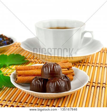 Tea cup, chocolates and cinnamon on bamboo mat on white background