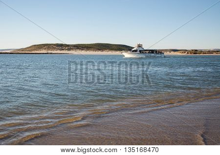 KALBARRI,WA,AUSTRALIA-APRIL 21,2016: Reefwalker charter boat heading out on the Murchison River with coastal dunes under a blue sky in Kalbarri, Western Australia.
