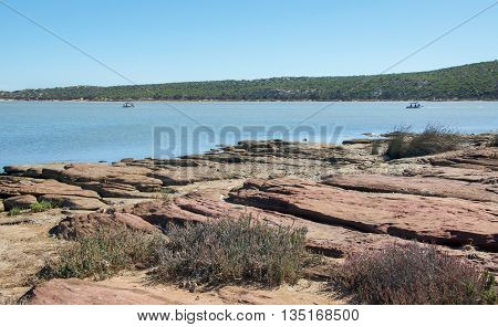 Murchison River rocky riverbank with sandstone formations, boats and coastal vegetated dunes under a clear blue sky in Kalbarri, Western Australia.