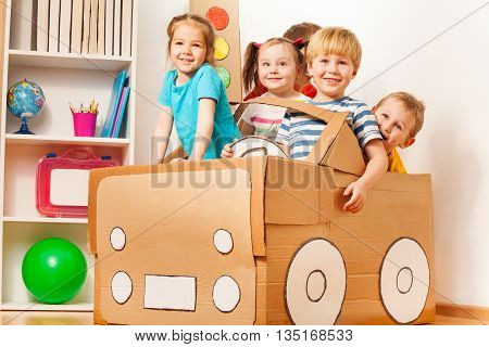 Smiling 5 years old boy drives his friends in toy cardboard car at the kindergarten