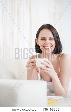 Lounging with good book. Mature woman drinking tea and reading book on couch, smiling and looking at camera