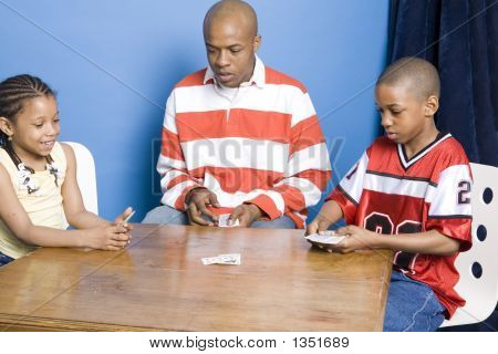 Father And Children Playing Cards