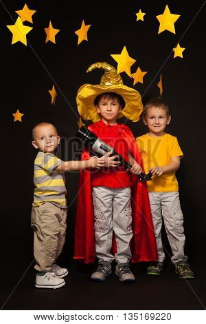 Full length photo of three age diverse boys, playing stargazers with a telescope, standing against black background with paper stars above