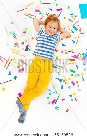 Top view of smiling pupil having rest laying among heap of stationery