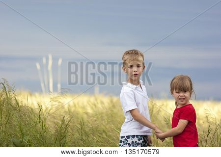 Little boy and little girl holding hands looking very displeased and dissatisfied