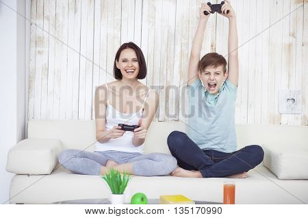 I love this game. Smiling woman and young boy in living room with console, playing video game