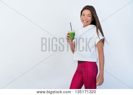 Woman drinking vegetable Green detox smoothie after fitness running workout on summer day. Fitness and healthy lifestyle concept with beautiful fit mixed race Asian Caucasian model