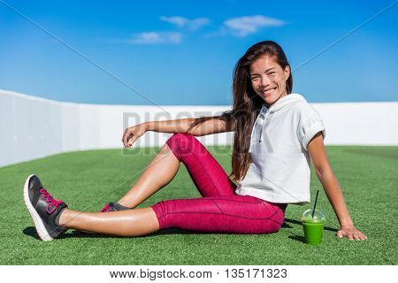 Healthy fitness Asian girl drinking green smoothie. Cute happy smiling woman relaxing during cardio training workout on outdoor grass gym enjoying vegetable juice morning breakfast in activewear.