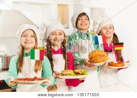 Four young cooks holding plates with traditional food of European states and USA in the kitchen