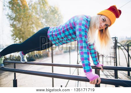Young beautiful woman doing push ups on parallel bars at calisthenics park, looking at the camera