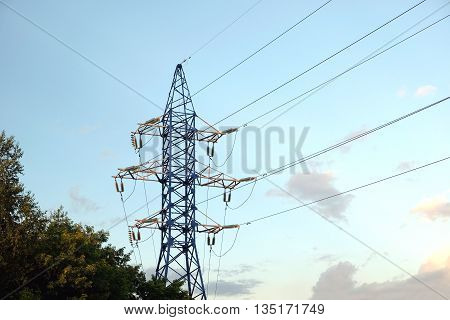 High-voltage power line metal prop with wires over cloudy blue sky in the evening horizontal view
