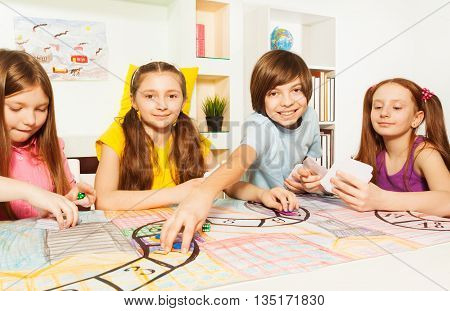 Smiling boy making his move, playing the tile game, sitting at the gaming table with his friends