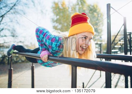 Young beautiful woman doing push ups on parallel bars at calisthenics park, looking off the camera