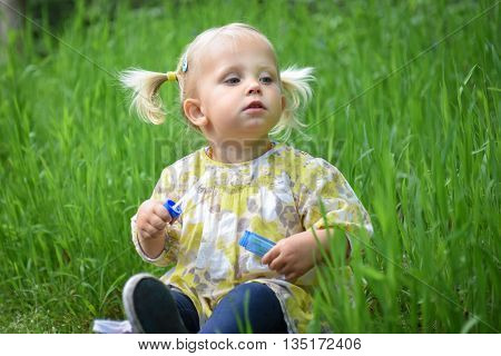 Beautiful Baby Girl Playing With Soap Bubbles In The Park.