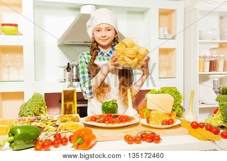 Girl in white apron and cook's hat making pasta, holding glass bowl with fettuccine at the kitchen