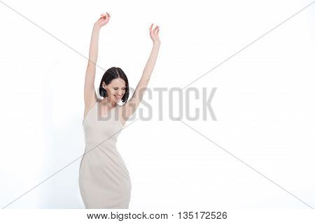 Enjoying victory. Successful woman celebrating with arms up, isolated on white background