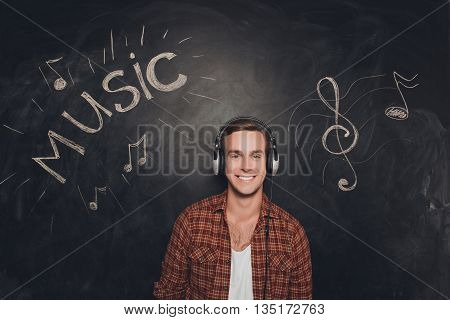 Pretty Smiling Young Man Listening Music In Headphones