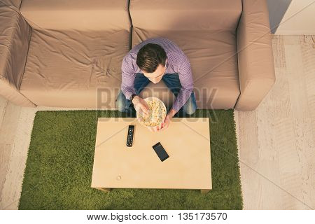 Top View Of Young Man Resting At Home While Watching Film And Eating Popcorn
