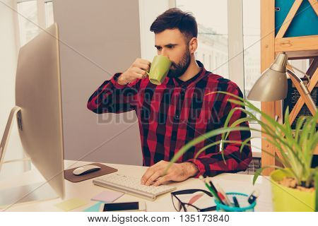Portrait Of Young Man Drinking Coffee And Typing On Keyboard