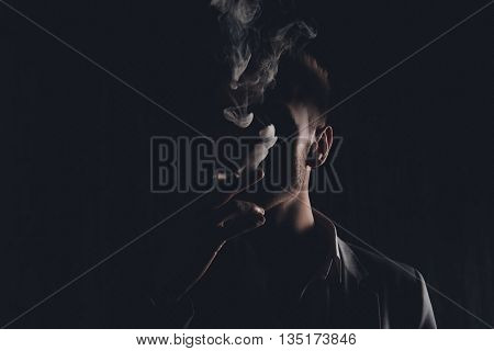 Mystery man with cigar and smoke isolated on black background