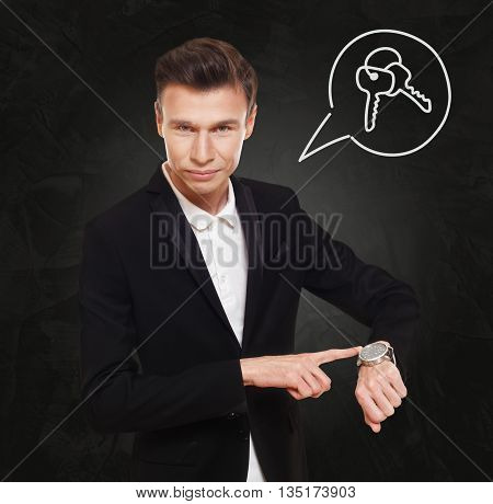 Time is money. Businessman point at his watch showing time is money, real estate buying concept. Man in suit with watch at black background, thinking cloud with keys. Rent, lease, sell property.