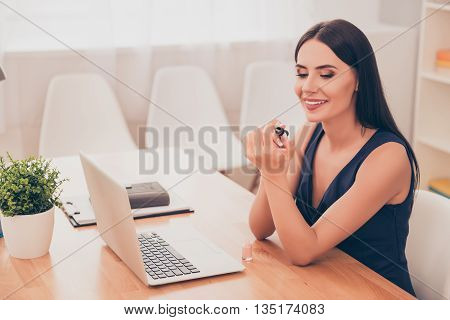 Smiling Pretty Secretary Sitting With Laptop And Doing Manicure