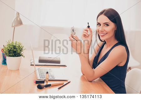 Portrait Of Happy Businesswoman Holding Brush Of Mascara And Mirror