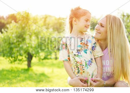 Mother and daughter outdoors. Image with natural sunflare