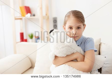 She loves her teddy. Portrait of cute little girl hugging her teddy bear, sitting on sofa