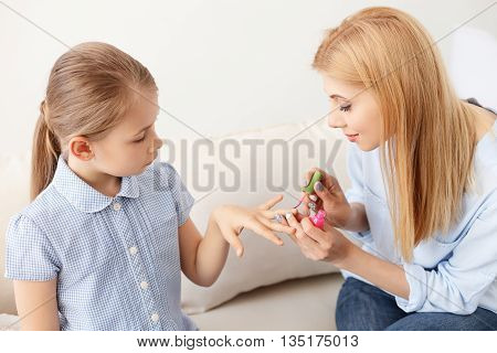 Most trendy color. Young beautiful mother painting nails of her pretty daughter, sitting on sofa