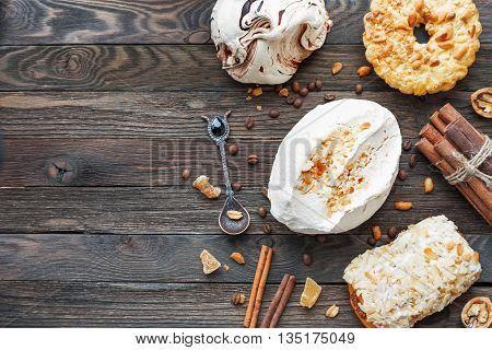 Rustic wooden background with different pastries - chocolate and peanut meringue tart marzipan bun. Different spices - cinnamon walnuts peanuts ginger. Top view of tasty desserts. Place for text.