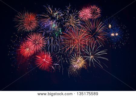 Beautiful celebration golden red blue sparkling fireworks over starry sky. Holidays symbol background. Independence Day 4th of July holidays salute. New Year beautiful fireworks.