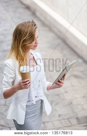Beautiful young businesswoman with a disposable coffee cup holding tablet in her hands