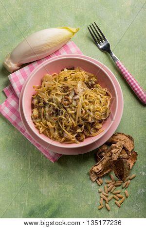 tagliolini with dried mushroom pinenuts and endive salad