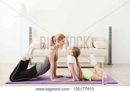 Passing on her love of yoga. Mother and daughter doing exercise home, lying on floor on mat