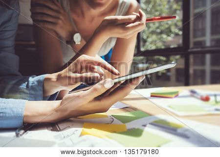 Closeup image Girl Touching Screen Digital Tablet Hand.Project Producers Researching Process.Young Business Crew Working New Startup modern Studio.Analyze market stocks.Blurred, film effect.Horizontal